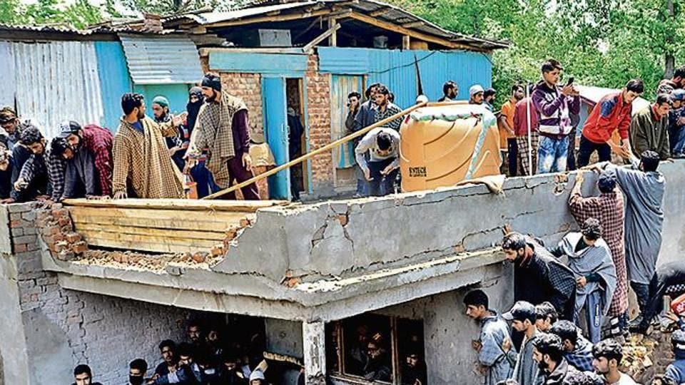 People gather at the broken house where Hizbul Mujahideen militants were killed in Panzgam area of Pulwama