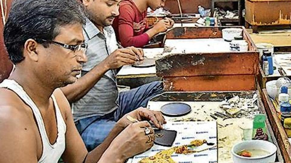 Artisans at work at a small unit that handles gold and silver ornamental work in Regar Pura in Karol Bagh, in New Delhi