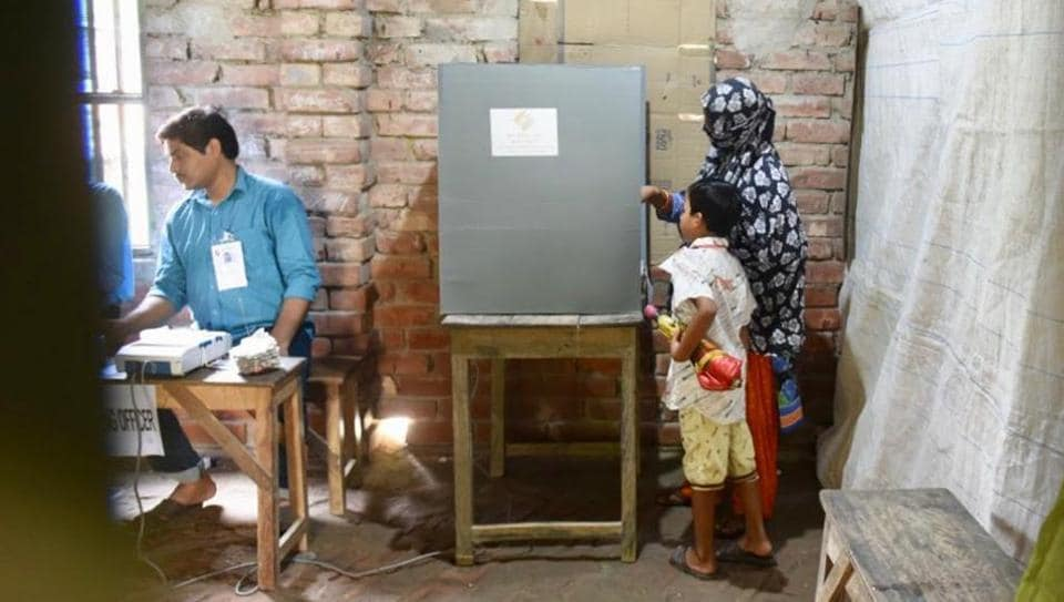 A woman casting her vote as her son looks in during the last phase of Lok Sabha poll at Banganagar in Diamond Harbour constituency , West Bengal on Sunday.