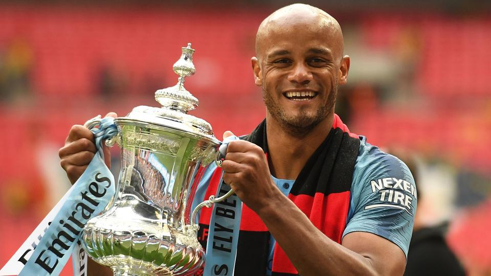 Manchester City's Belgian captain Vincent Kompany holds the winner's trophy after the English FA Cup final.