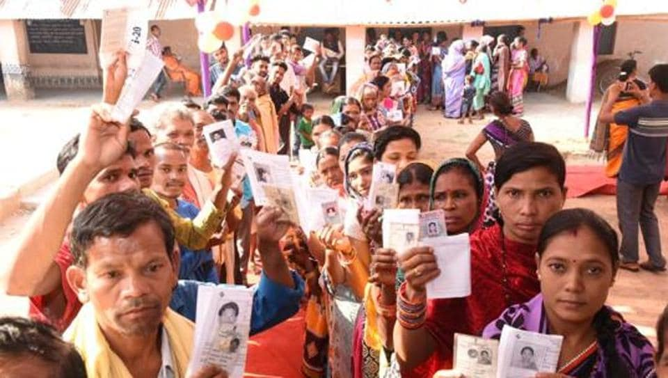 Voters show their identity cards as they stand in queues to cast their votes in Odisha.