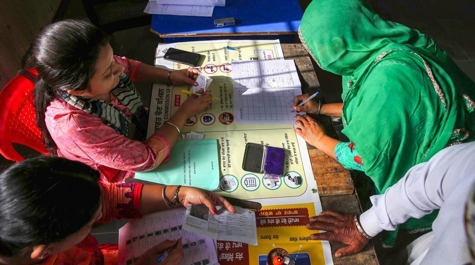 A voter signs a document after casting her vote at a polling station during the seventh and last phase of Lok Sabha elections, at village Bhoot, near Amritsar, Sunday, May 19, 2019.