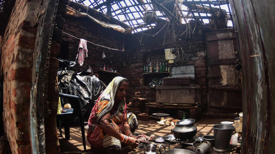 A woman cooks inside her house destroyed by the cyclone 'Fani' in the Pratap Purushottampur village area of Puri in the eastern Indian state of Odisha on May 10, 2019.