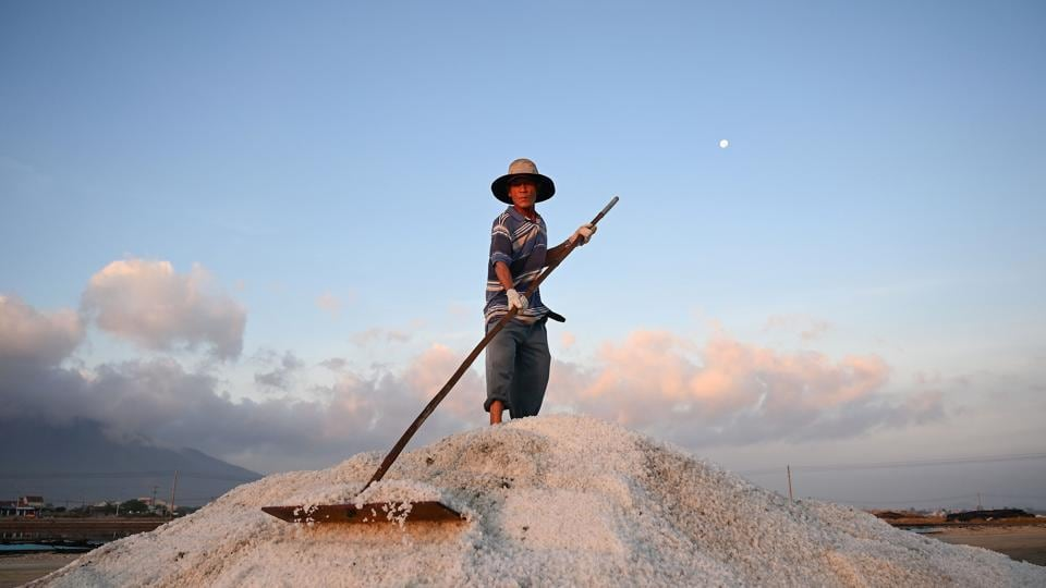 A worker harvests salt in southern Vietnam's Hon Khoi salt fields. Like their ancestors, the salt farmers of the area rise before dawn each day, fan out across shallow seawater pools o harvest the precious mineral, in the hope for a better season than the last. Amid punishing work and unstable incomes, the farmers work under increasingly unpredictable weather patterns to make a living. (Manan Vatsyayana / AFP)