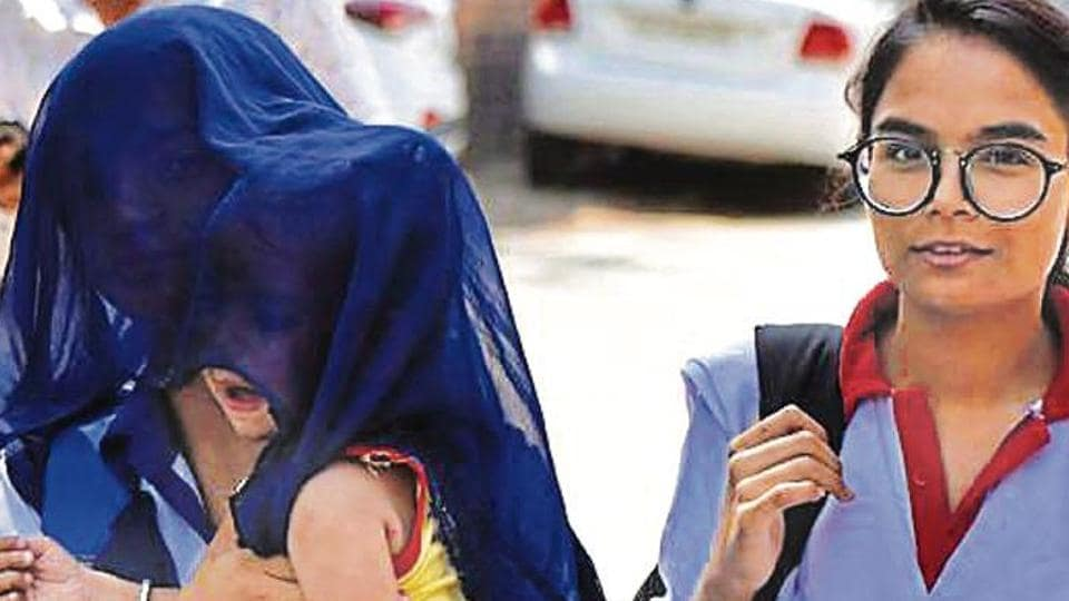 A woman shields her child from the sun on Monday, when the day temperature soared in Gurugram