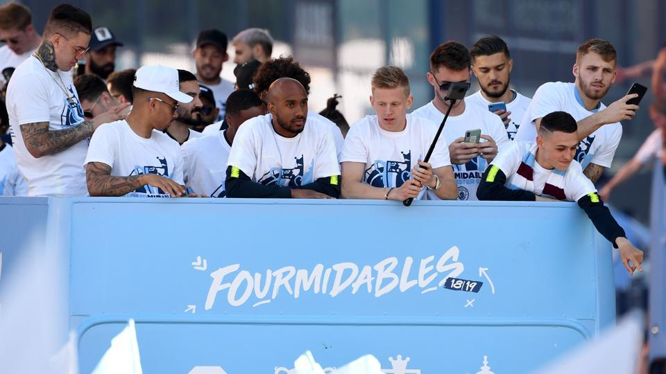 Manchester City players, including Manchester City's Brazilian goalkeeper Ederson (L) and Manchester City's English midfielder Fabian Delph (C), Manchester City's Ukrainian midfielder Oleksandr Zinchenko (center R) and Manchester City's English midfielder Phil Foden (R) take part in an open-top bus parade through Manchester