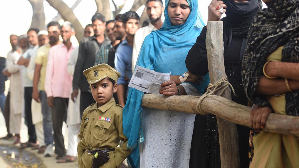 Uttar Pradesh, the state with 80 constituencies -- the maximum among all the others – witnessed polling in multiple phases. During the inaugural phase on April 11, a boy was seen dressed as a defence personnel while people queued to cast their votes at Sawal village. (Raj K Raj / HT Photo)