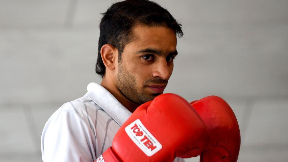 Indian boxer Amit Panghal poses for photographs wearing his gloves during a felicitation ceremony.