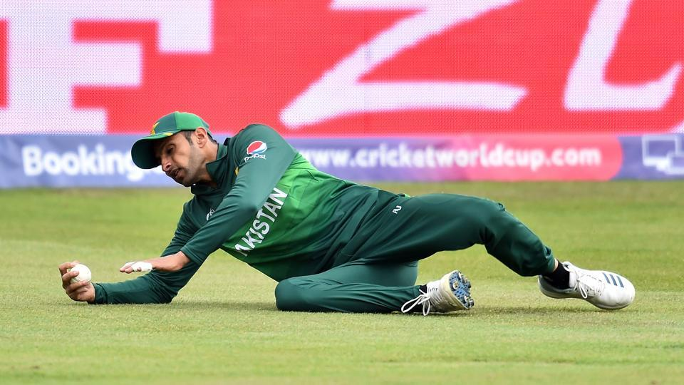 Pakistan's Shoaib Malik dives to make a catch and take the wicket of Afghanistan's Hazratullah Zazai for 49 runs. (AFP)