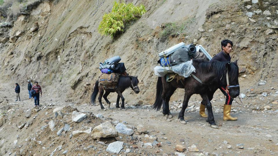 Polling workers trek to transport Electronic Voting Machines (EVM) and Voter-Verified Paper Audit Trail (VVPAT) machines to a remote polling station –one of a million organised –in Srikhola at an altitude of 2,800 metres above sea level near the India-Nepal border in West Bengal. From cities and villages to remote islands and dense jungles, the 2019 polls saw polling last seven phases spread over 39 days. (Diptendu Dutta / AFP)