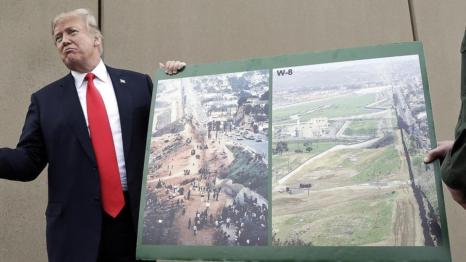 US president Donald Trump holds a poster with photographs of the US. - Mexico border area as he reviews border wall prototypes in San Diego with Rodney Scott.