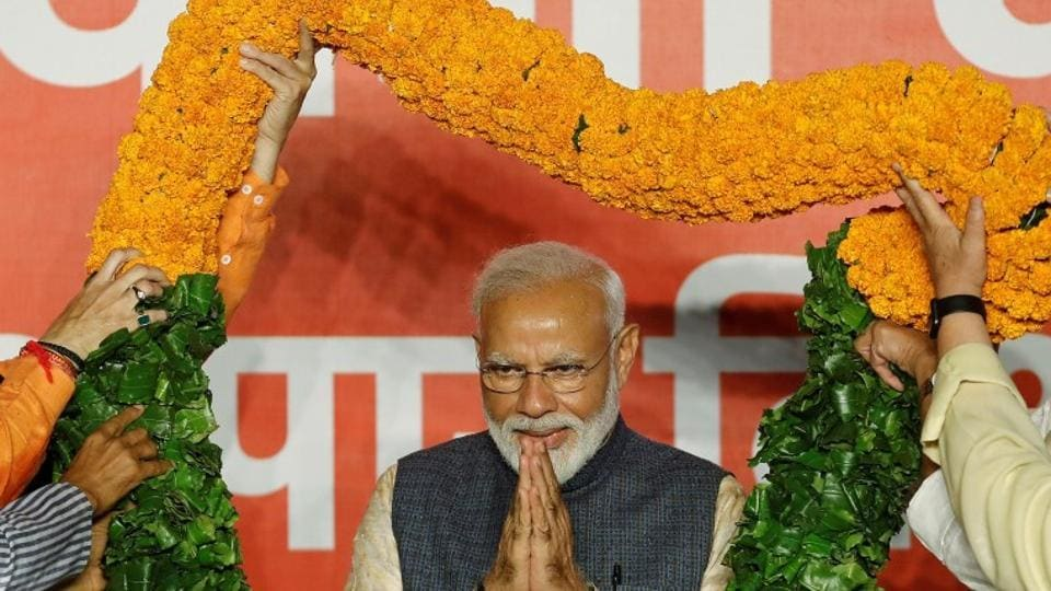 Indian Prime Minister Narendra Modi gestures as he is presented with a garland by Bharatiya Janata Party (BJP) leaders after the election results in New Delhi, May 23, 2019.
