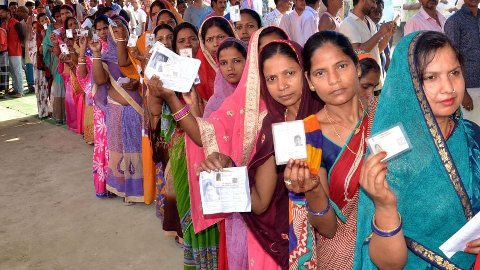 Voters show their ID cards as they wait in a queue to cast vote at a polling station.