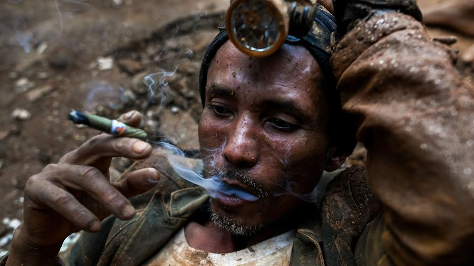 "A miner rests as he smokes a cigar at a ruby mine. Despite slim pickings, the lure of a quick profit is difficult to resist. One worker told AFP his team of five had only found one gemstone in a month, which they sold for just 100,000 kyat ($65). ""We've spent about 600,000 kyat on petrol and machines so far,"" he lamented, adding they are simply unable to dig deep enough. (Ye Aung Thu / AFP)"