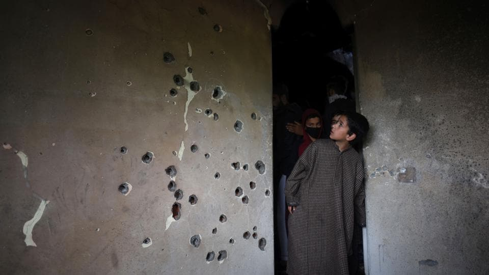 A boy looks at a bullet-riddled wall of a residential house that was damaged during a gun battle between militant commander Zakir Musa and security forces, at Dadasara village, in Tral, Jammu and Kashmir. (Waseem Andrabi / HTPhoto)
