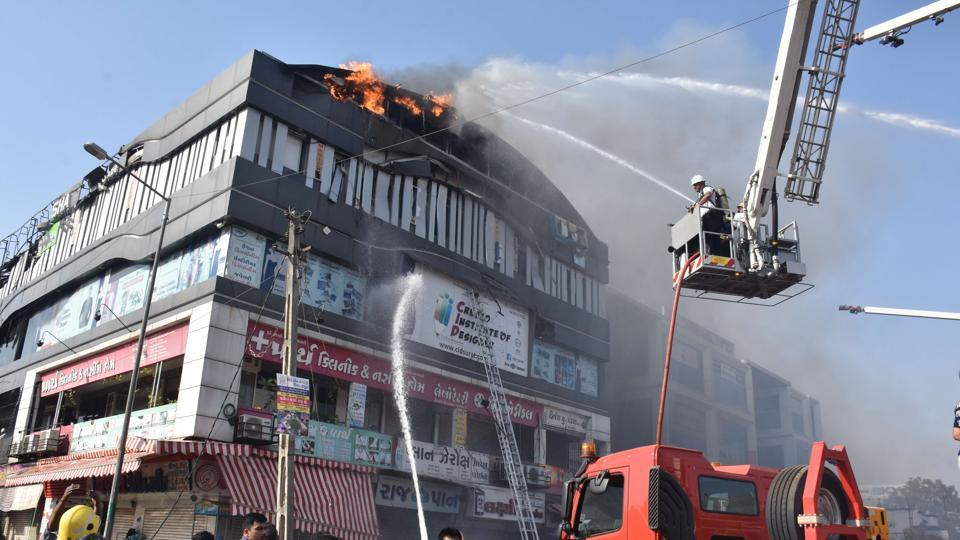 Firefighters fighting the blaze at Takshila complex  inSurat in which 23 students died.