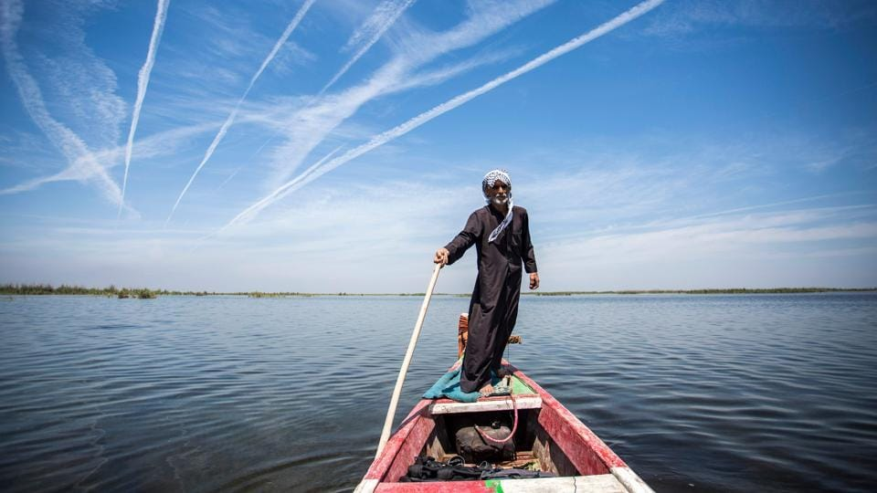 "Abu Hayder, an ecotourism guide, navigates a canoe in the marshes of Chibayish in Iraq. ""I didn't think I would find somewhere so beautiful, and such a body of water in Iraq,"" said Habib al-Jurani. He left Iraq in 1990 for the United States, and was back for a family visit. Looking around the lush marshes, declared in 2016 to be Iraq's fifth UNESCO World Heritage site, Jurani added: ""There are some mesmerising places.""  (Hussein Faleh / AFP)"