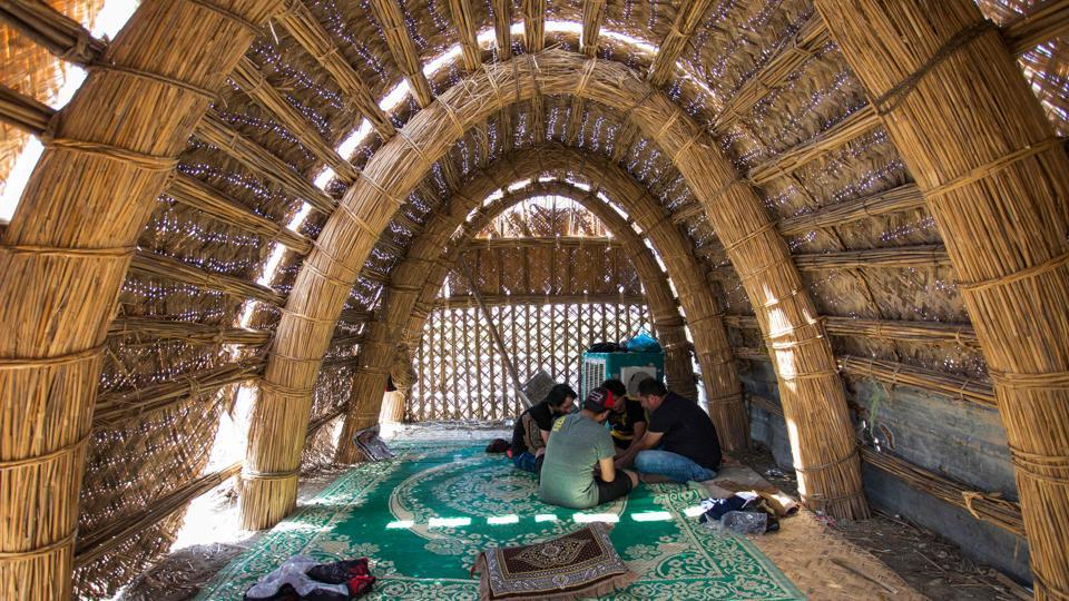 "Tourists sit inside a floating palm reed-woven house in the marshes. It all culminated with a particularly dry winter last year that left the ""ahwar"", as they are known in Arabic, painfully parched. But heavier rains this year have filled more than 80% of the marshes' surface, according to the UN, compared to just 27% last year. That has resurrected the ancient lifestyle that dominated this area for more than 5,000 years.  (Hussein Faleh / AFP)"