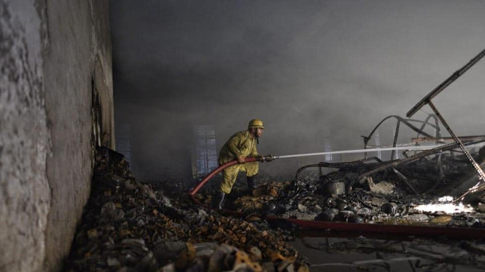 Fire fighters dozing off the fire in a headlight making factory for motor vehicles in Udyog Nagar near Peeragarhi, New Delhi.