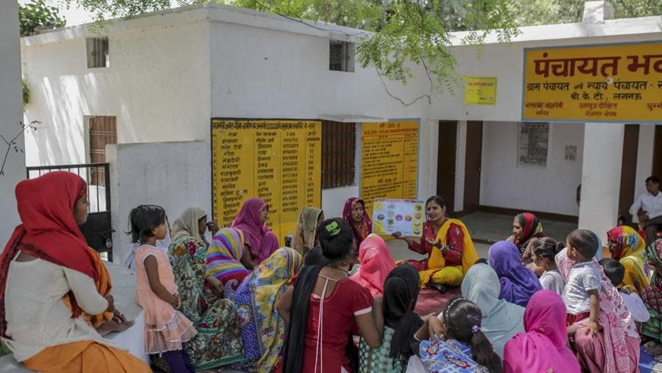 """What do you do when you are expecting guests in the house?"" Anju Maurya (C, right), a block coordinator with WaterAid India and its partner asks a group of women of all ages under a shady tree in front of village Panchayat Office in Sonva, Bakshi Ka Talab block of Lucknow, Uttar Pradesh. ""I prepare some nice food,"" one lady pipes up. ""I make sure my house is clean,"" says another. (WaterAid / Dhiraj Singh)"