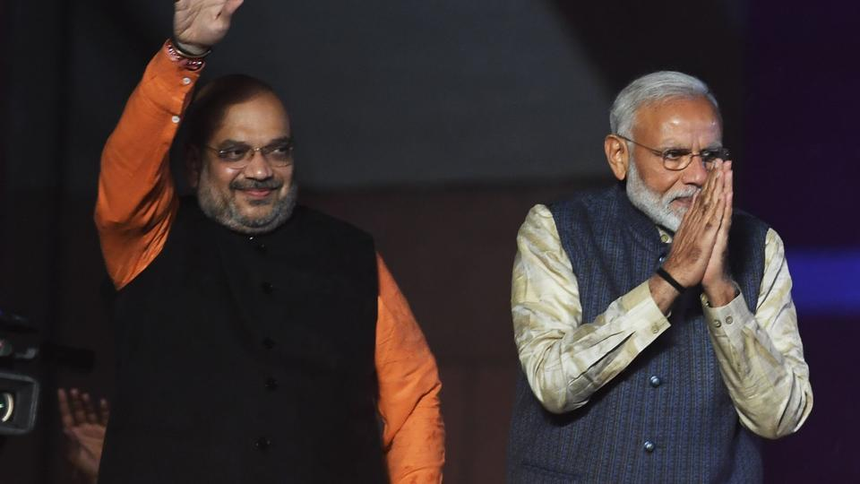 PM Narendra Modi (R) and Bharatiya Janta Party (BJP) president Amit Shah gesture to supporters as they celebrate the victory in India's general election at the party headquarters in New Delhi on May 23, 2019.