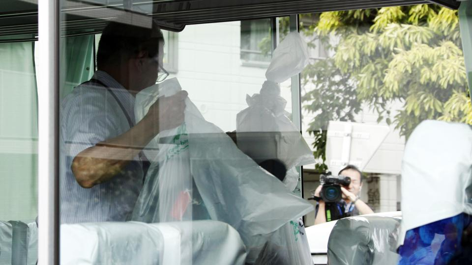 An investigator holds plastic bags containing school students' belongings inside their school bus at the scene where a man wielding a knife attacked commuters in Kawasaki, near Tokyo Tuesday.