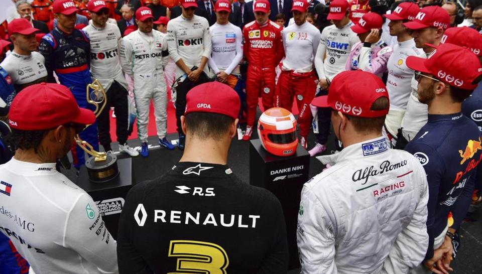 The drivers clap hands around a red helmet on a podest, reading 'Thank you Niki', during a minute of silence to tribute F1 legend Niki Lauda prior the Monaco Formula One Grand Prix race, at the Monaco racetrack
