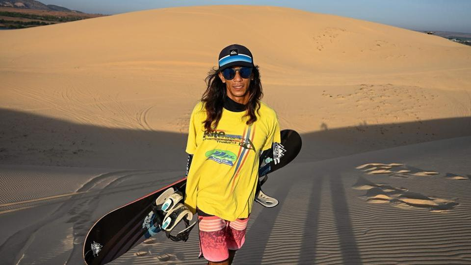 """It's been an uphill battle for athletes like him facing funding shortfalls, lack of public interest and few training facilities, namely snowy mountains. """"This sport is so new for Vietnamese, and we don't have any snow to practise on,"""" said 29-year-old Binh, looking California cool in a Quicksilver cap and bright boardshorts. (Manan Vatsyayana / AFP)"""