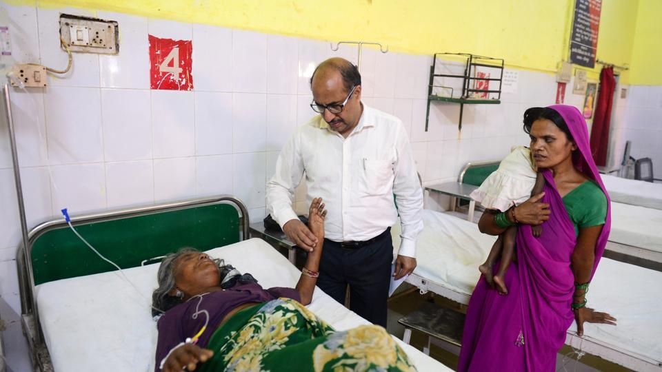 "Chief medical officer Doctor Anil Agarwal (C) during his inspection round in a hospital at Sitapur, Uttar Pradesh. ""This scheme has infused a sense of belief in the poor that if they fall sick they will get treatment without spending a rupee,"" Agarwal said. Voting data from the election that ended last week showed particularly strong support for Modi's BJP in poorer areas where people would have benefited most. (Sanjay Kanojia / AFP)"