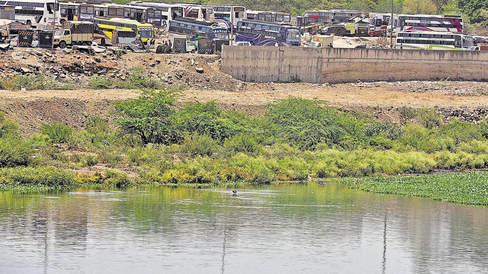 Civic activists say that the land near river at Sangamwadi, reclaimed by filling it with debris, is used for various purposes, including parking of luxury buses.