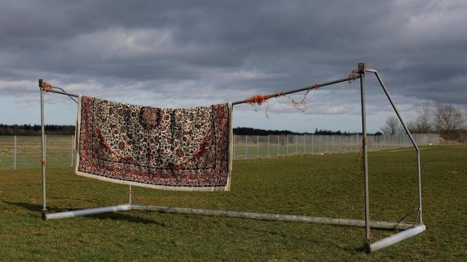"A rug belonging to a resident from Iran hangs from a football goalpost to dry. Yasaman Paknejad, 36, came to Denmark from Iran to study. She said she is a refugee based on the political situation in Iran, but her asylum case was rejected. ""I have no freedom in here, and it is breaking me down mentally. Regular prisoners know when they will be set free, so this is far worse than being in prison."" (Andrew Kelly / REUTERS)"
