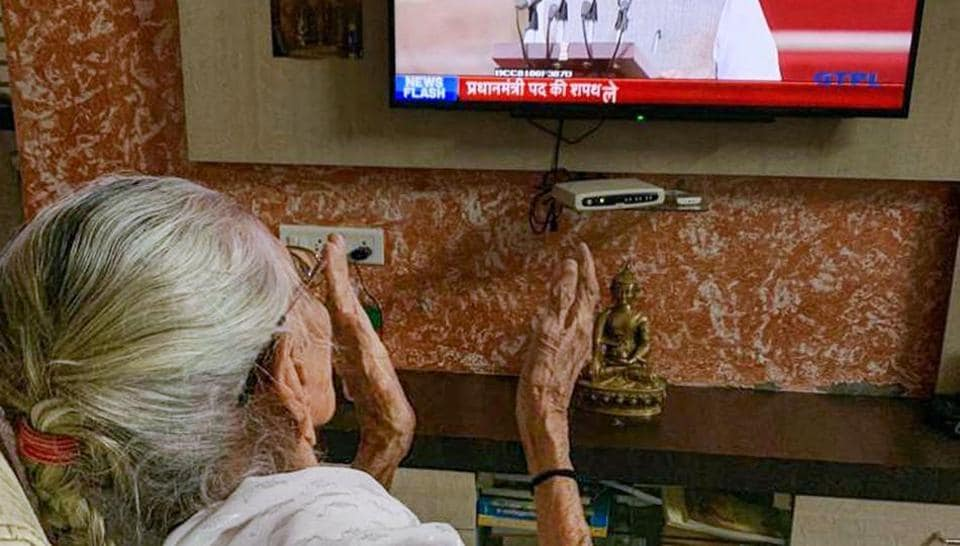 Prime Minister Narendra Modi's mother Hiraba watches him on television as he takes oath of office and secrecy for the second term, at her residence in Gandhinagar, Thursday, May 30, 2019.