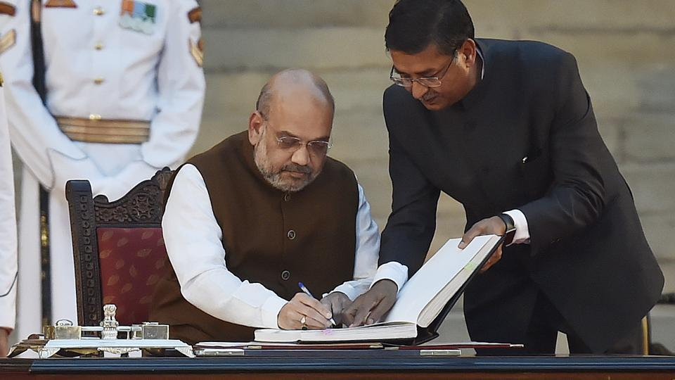 Bharatiya Janata Party (BJP) chief Amit Shah signs the documents after taking oath during a swearing-in ceremony, at the forecourt of Rashtrapati Bhavan in New Delhi, on Thursday, May 30, 2019.