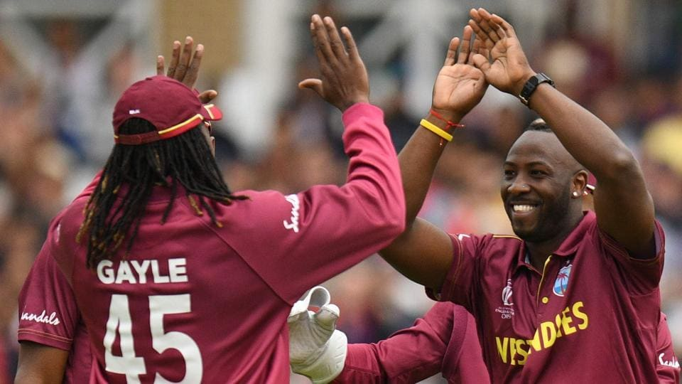 West Indies' Andre Russell (R) celebrates with West Indies' Chris Gayle (L) after taking a wicket.