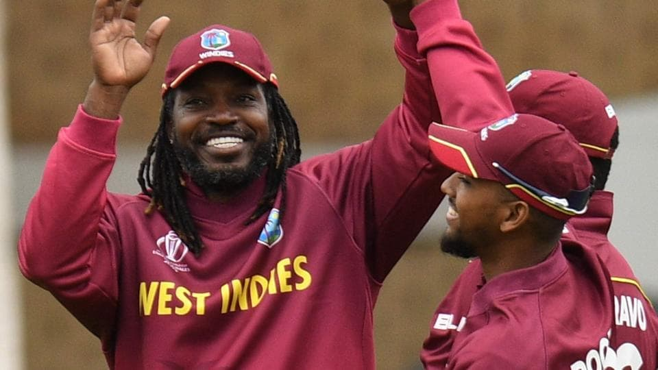 West Indies' Chris Gayle (L) celebrates taking the catch to dismiss Pakistan's Imad Wasim.
