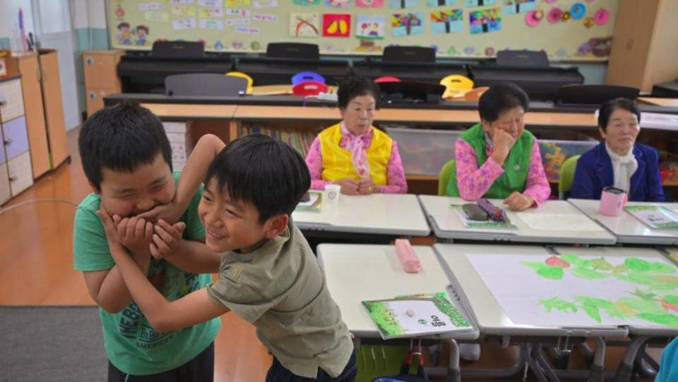 "(L-R) Park Young-ae, Nam Yang-soon and Shin Dong-hee with their classmates. Eight-year-old fellow pupil Kim Seung-hyun addresses his ageing friends with the honorifics that Korean requires for elders, but hopes they will continue all the way through sixth grade, when primary school finishes, and on to middle school with him. ""I think I would be sad if they stopped coming to school,"" he said. (Jung Yeon-je / AFP)"