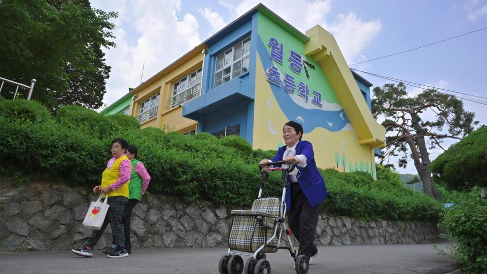 "(L-R) Park Young-ae, Nam Yang-soon and Shin Dong-hee head home after school. At least three other schools in South Jeolla are known to have recruited grandmothers, but a provincial official declined to say how many had done so altogether, or how many grandmothers had enrolled, ""especially as we don't have countermeasures to the falling number of students in rural areas,"" she said. (Jung Yeon-je / AFP)"