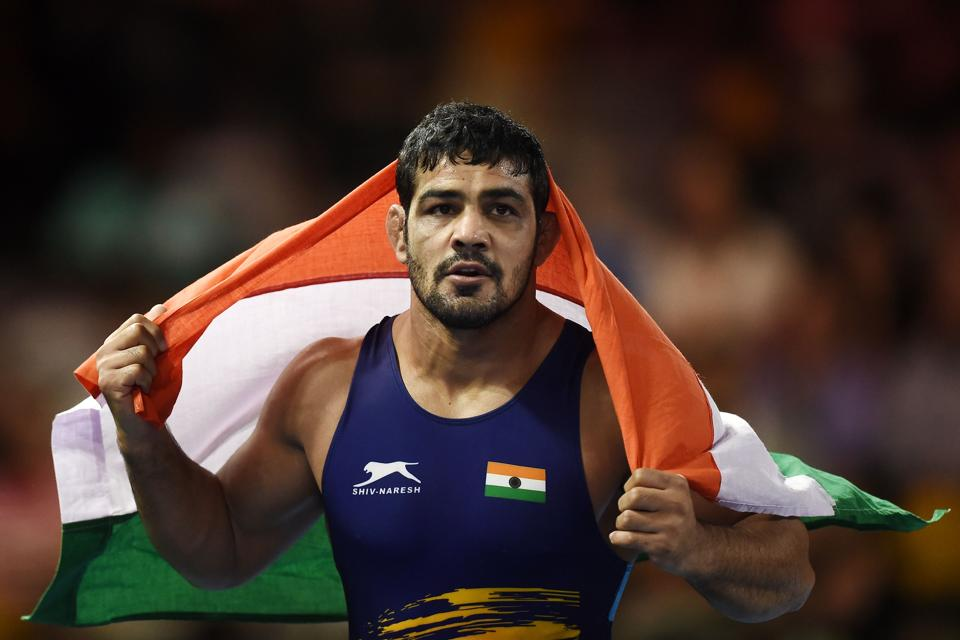 India's Kumar Sushil celebrats with his flag after wrestling against South Africa's Jahannes Botha during the men's freestyle 74 kg gold medal wrestling match at the 2018 Gold Coast Commonwealth Games in the Carrara Sports Arena on the Gold Coast on April 12, 2018.