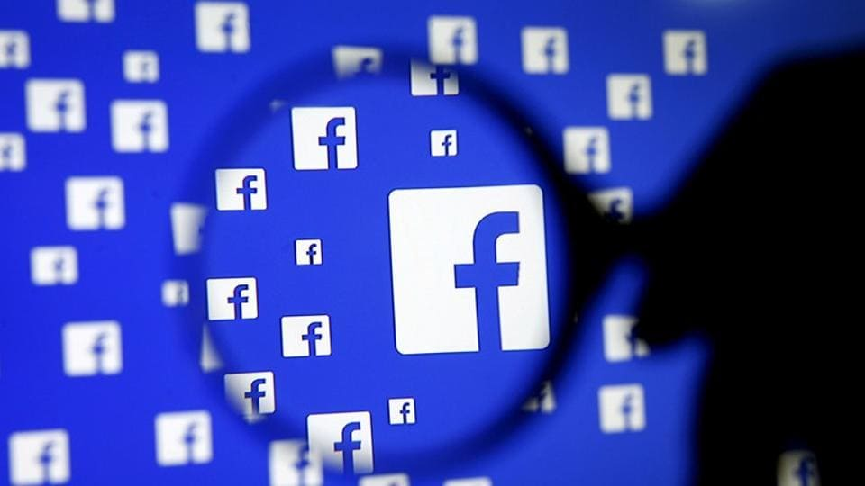 A man poses with a magnifier in front of a Facebook logo on display in this illustration taken in Sarajevo, Bosnia and Herzegovina, December 16, 2015.