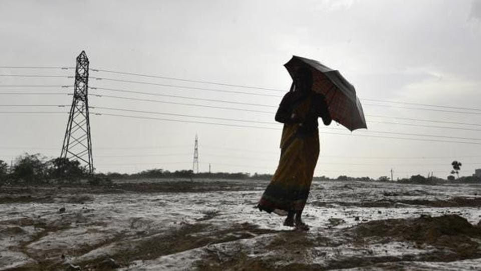 A woman walks with an umbrella in an open field during sudden rain in New Delhi
