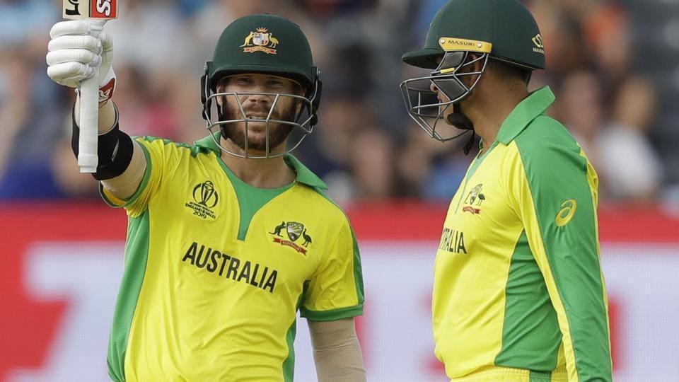 Australia's David Warner celebrates reaching 50 runs next to Australia's Usman Khawaja, right. (AP)