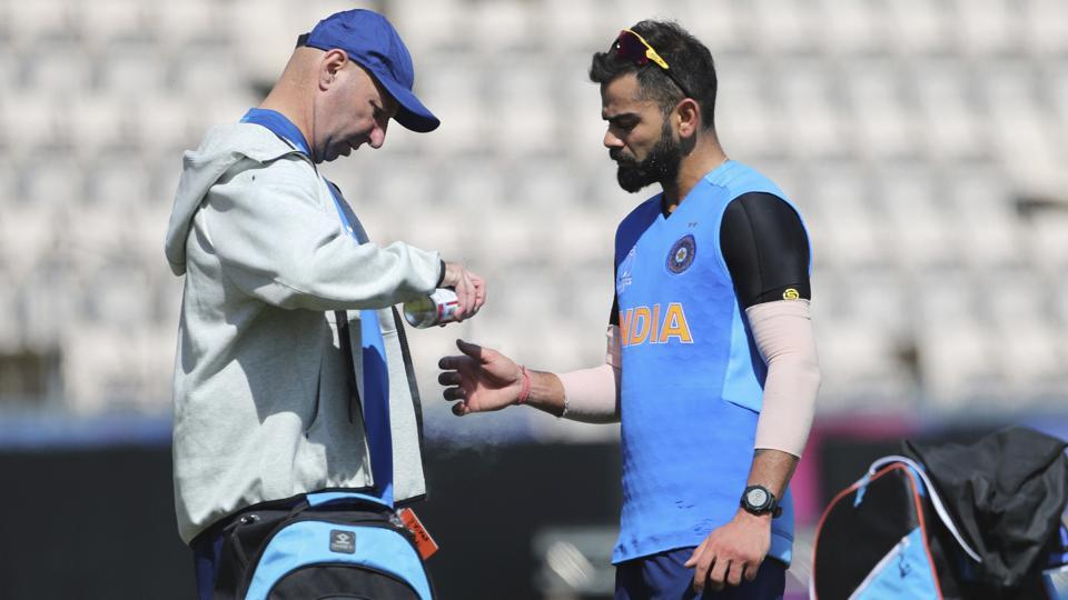Indian team physiotherapist Patrick Farhart, left, sprays the thumb of India's captain Virat Kohli after hurting it during a training session ahead of their Cricket World Cup match against South Africa at Ageas Bowl in Southampton, England, Saturday, June 1, 2019.