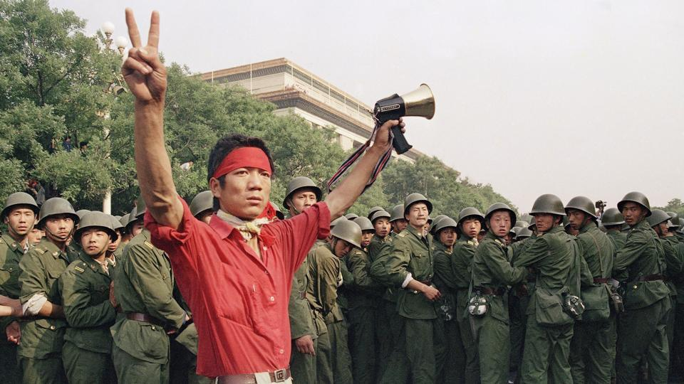 A student pro-democracy protester flashes victory signs to the crowd as troops withdraw near Tiananmen Square in Beijing on June 3, 1989. Corruption among the elite was a key complaint, but protesters were also calling for a more open and fair society, one that would require the Communist Party to relinquish control over many aspects of life, including education, employment and even the size of families. (Mark Avery / AP File)