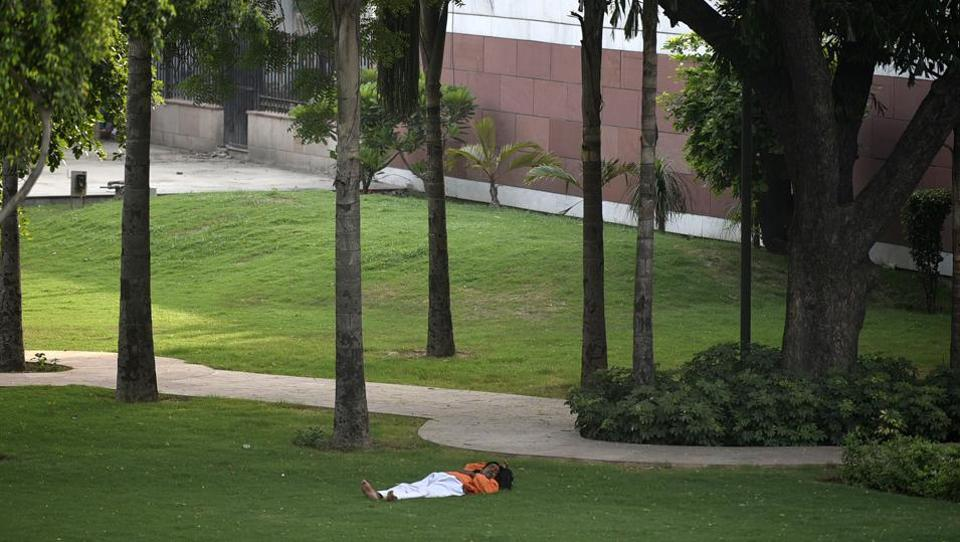 A man sleeps under the shade of tall trees on a hot summer day in New Delhi. A severe heatwave continued to sweep India's northern plains as 10 places in the region figured on the list of 15 hottest places in the world on Sunday. Rajasthan's Churu and Sri Ganganagar, where the mercury shot up to 48.9 and 48.6 degree Celsius, were the hottest places in the world. (Biplov Bhuyan / HT File)
