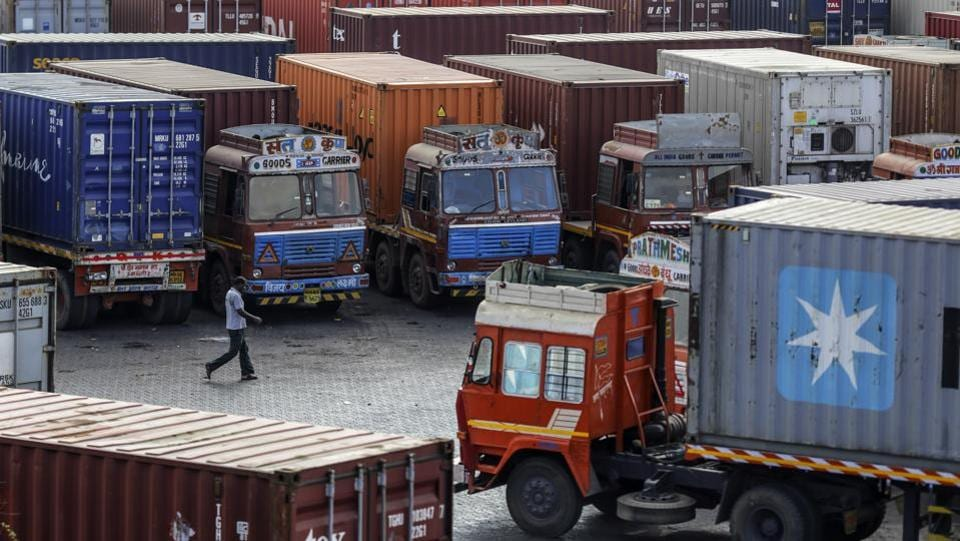 """A man walks past container trucks sitting parked near the Jawaharlal Nehru Port, in Navi Mumbai, Maharashtra. """"I have determined that India has not assured the United States that India will provide equitable and reasonable access to its markets,"""" Trump said in a proclamation on May 31. 2019. """"Accordingly, it is appropriate to terminate India's designation as a beneficiary developing country effective June 5, 2019."""" (Dhiraj Singh / Bloomberg)"""