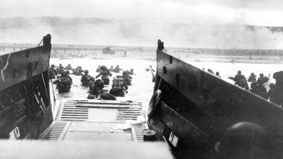 Under heavy German machine gun fire, American infantrymen wade ashore off the ramp of a Coast Guard landing craft during the invasion of the French coast of Normandy in World War II. June 6, 2019, marks the 75th anniversary of D-Day, the assault that began the liberation of France and Europe from German occupation, leading to the end World War II. (US Coast Guard via AP)