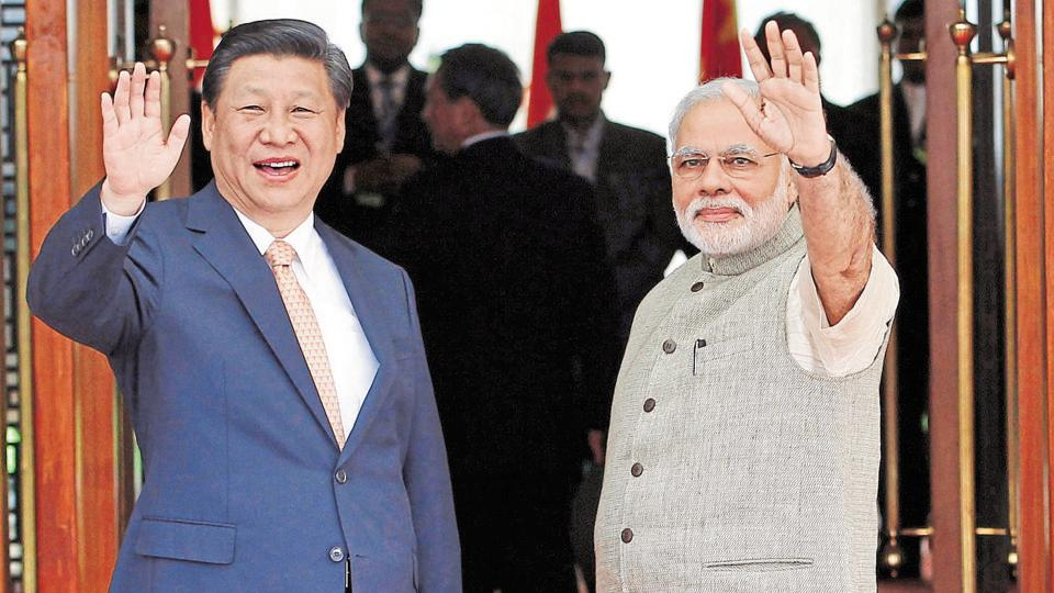 India's Prime Minister Narendra Modi (R) and China's President Xi Jinping wave before their meeting in the western Indian city of Ahmedabad on September 17, 2014.