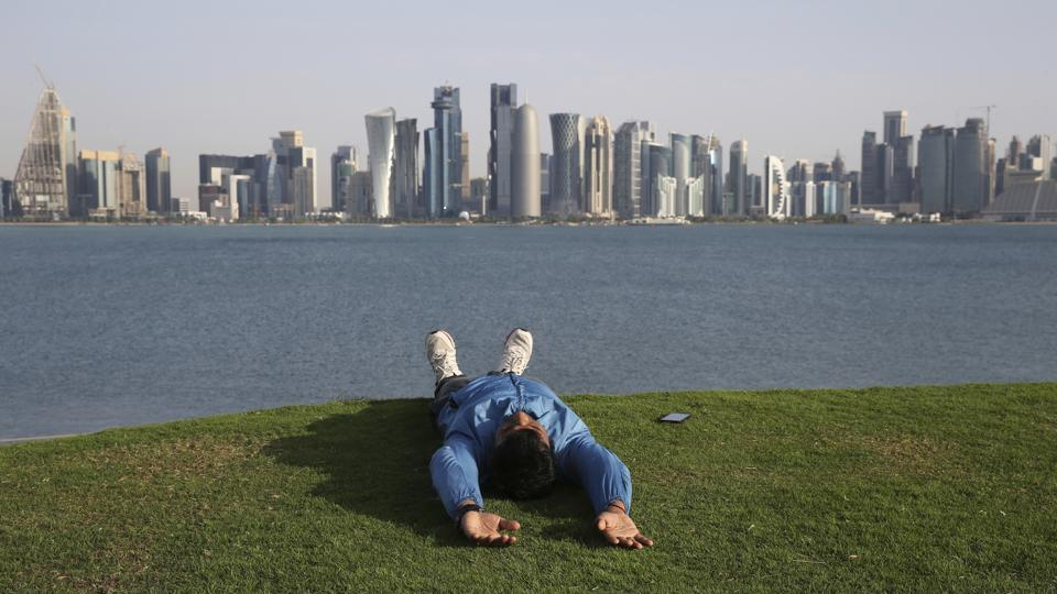 A man lies sprawled on a grass-covered hill at MIA park overlooking the skyline of Doha, Qatar. The gas-rich peninsular nation just 50 kilometers wide with a population of 2.7 million, will be the first Arab nation to host the World Cup. (Kamran Jebreili / AP)