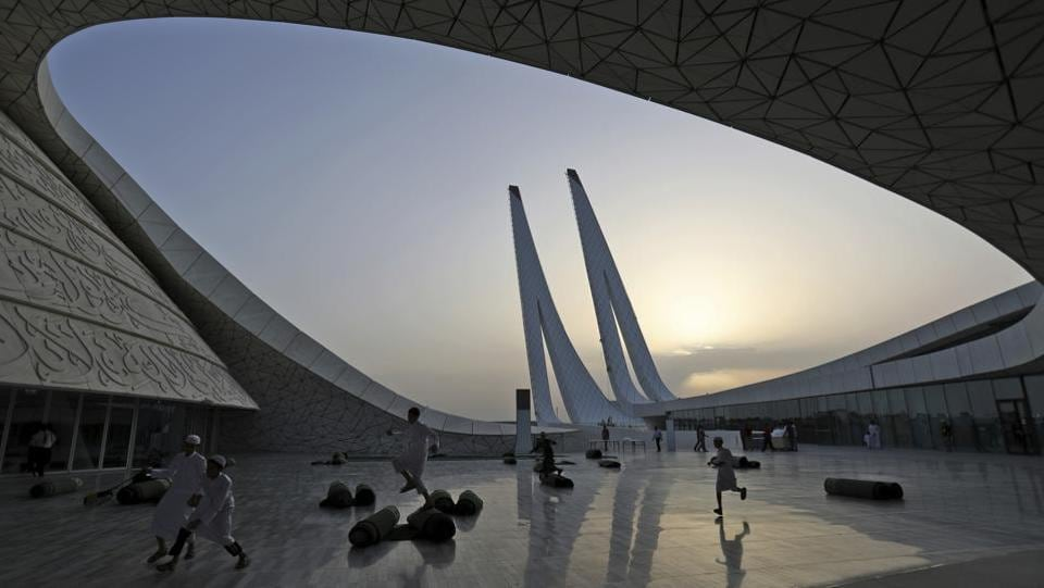 Students play in the Qatar Faculty of Islamic Studies in Doha, during sunset. Designed by Mangera Yvars Architects, the building's shape is conceptually based on the historical