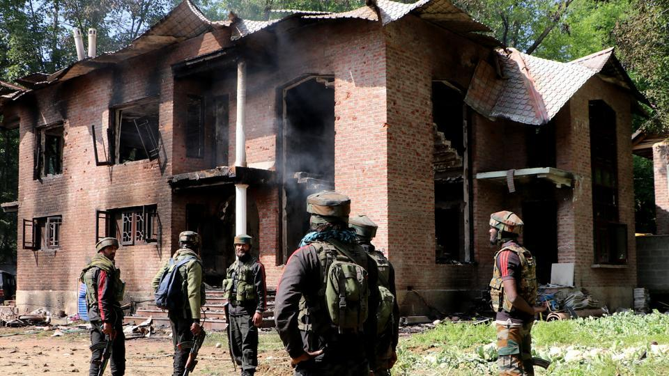 Army jawans stand guard outside a damaged house after a gun battle between militants and security forces at Panjran Pulwama district of south Kashmir on Friday. Four militants were killed in an encounter with security forces.